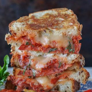 A crispy Italian grilled cheese sandwich stacked high alongside basil and chili.