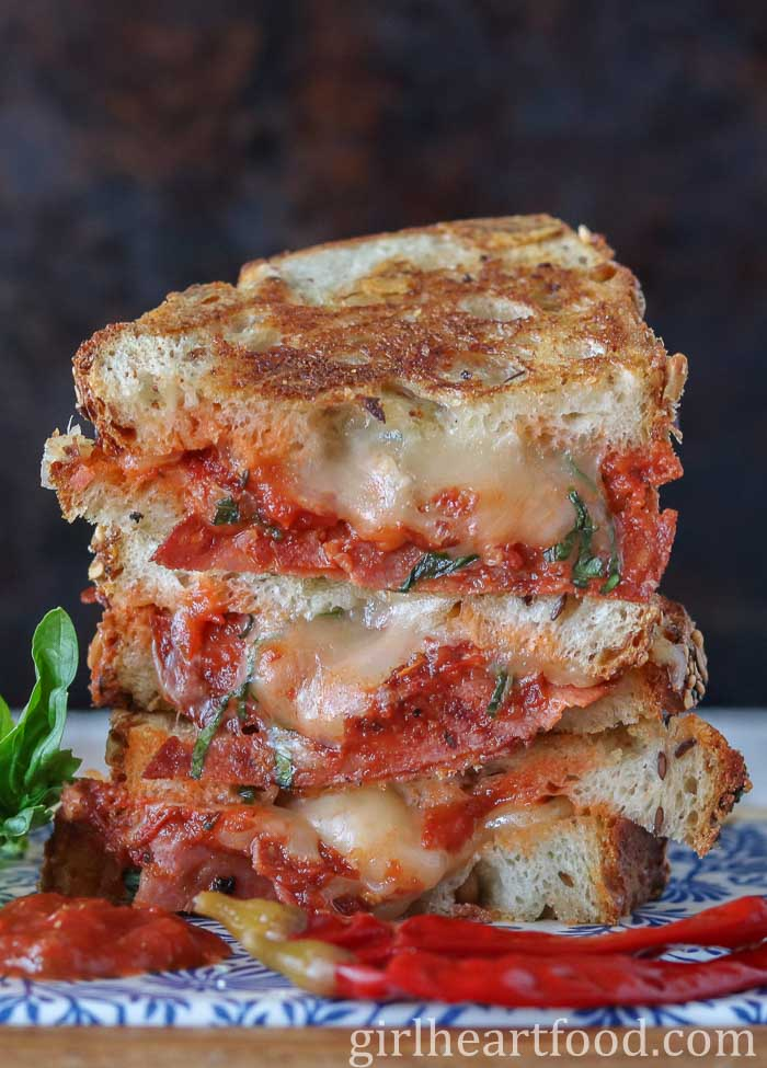 Stack of three pizza grilled cheese sandwich halves next to two red chili peppers, basil and pizza sauce.
