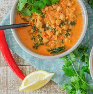 An overhead shot of a bowl of easy red lentil chickpea soup garnished with fresh cilantro.