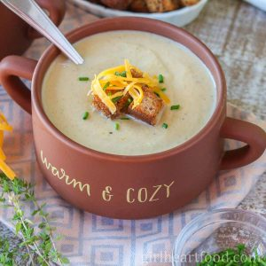 Bowl of creamy cauliflower leek soup garnished with croutons, chives and cheddar.