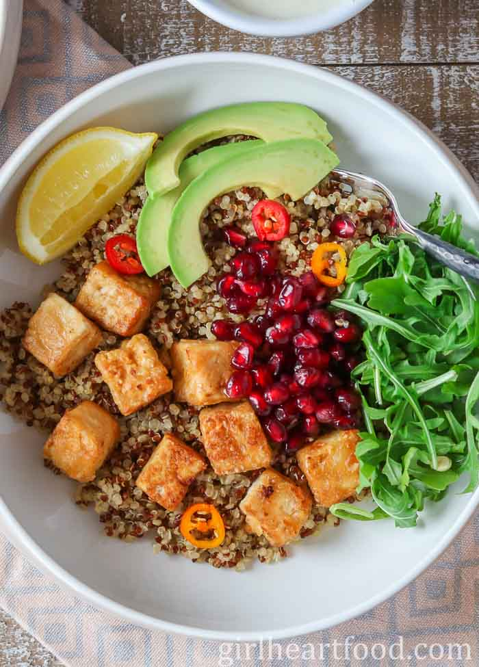White bowl with quinoa, crispy tofu, veggies and fruit.