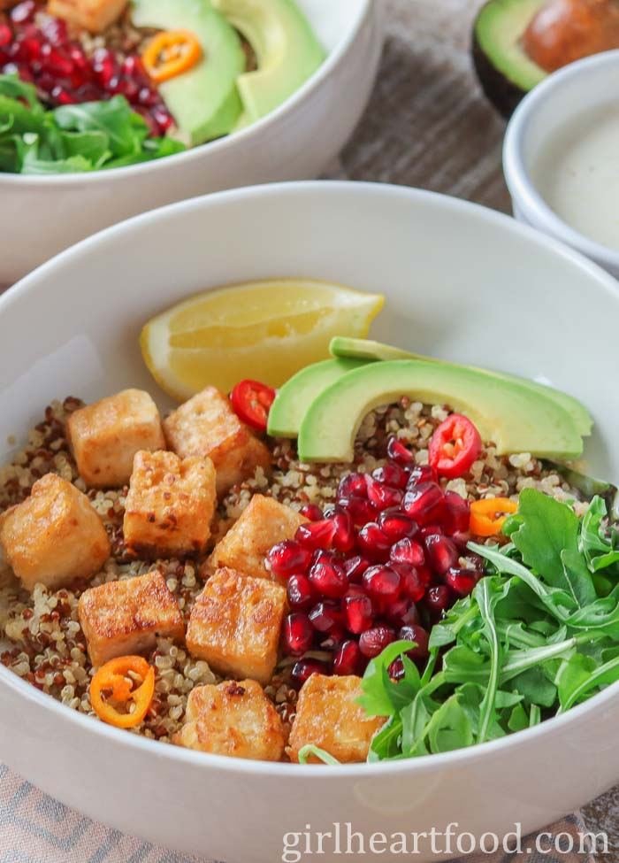 A quinoa tofu bowl garnished with chili, arugula, pomegranate and avocado.