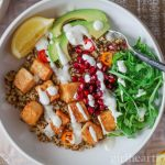 An overhead shot of an easy tofu bowl with quinoa drizzled with a garlicky yogurt sauce.