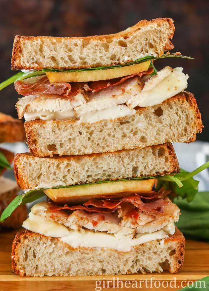 A chicken and prosciutto sandwich cut in half and pieces stacked on top of each other.