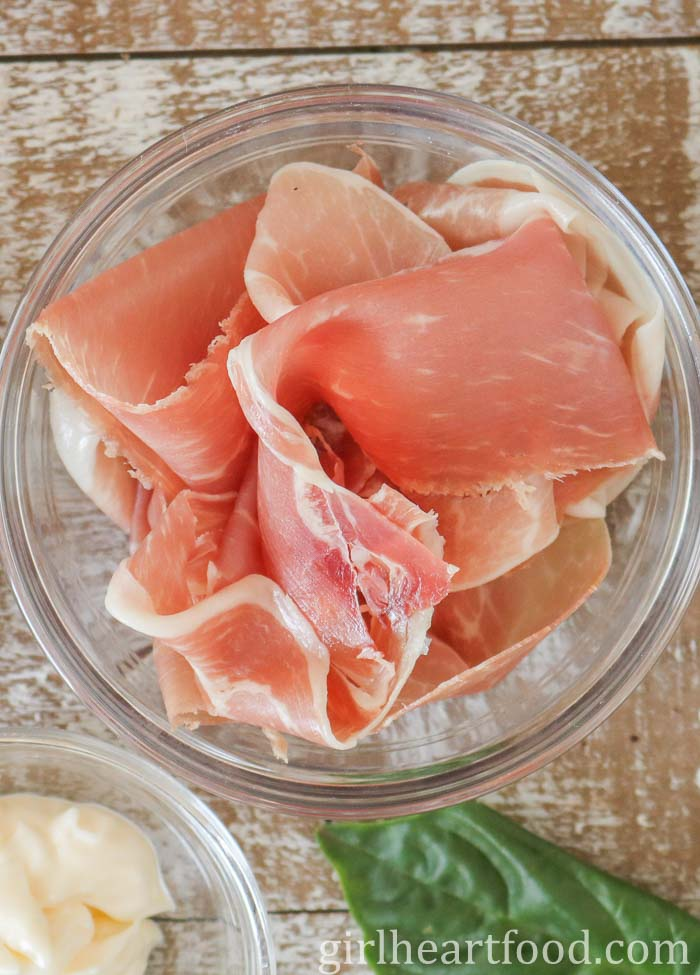 Slices of prosciutto in a small clear bowl.