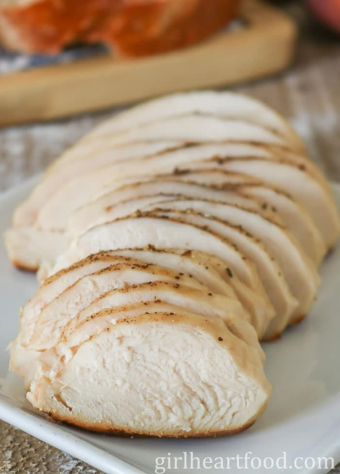 Sliced chicken breast on a white plate.