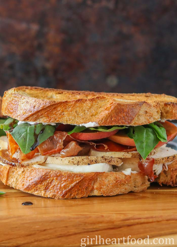 A chicken and prosciutto sandwich on a wooden board.