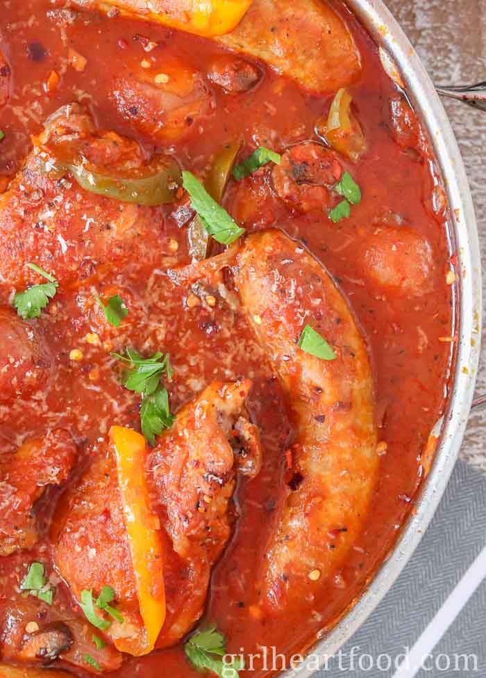 An overhead close up shot of a pan of Italian sausage and peppers with chicken in red sauce garnished with parsley.