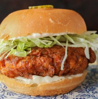 A fried chicken sandwich garnished with lettuce and a pickle slice.