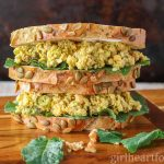 A stacked chickpea salad sandwich with kale on a wooden board.