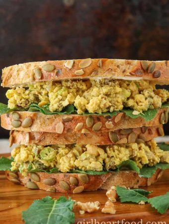 A stacked chickpea salad sandwich alongside baby kale and walnuts.