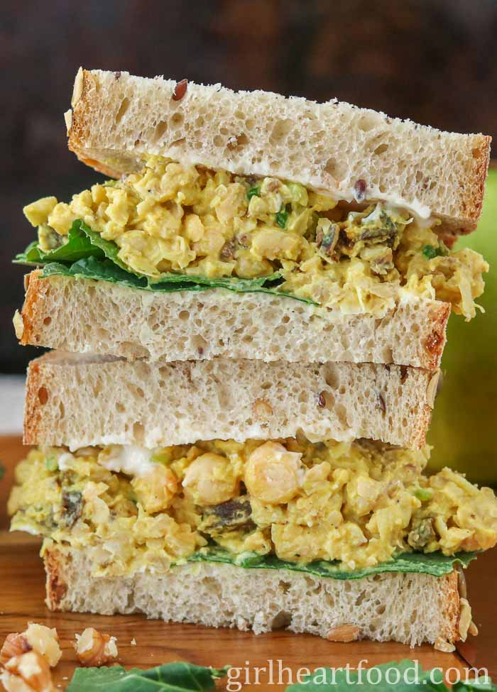 A stacked mashed chickpea salad sandwich garnished with kale.