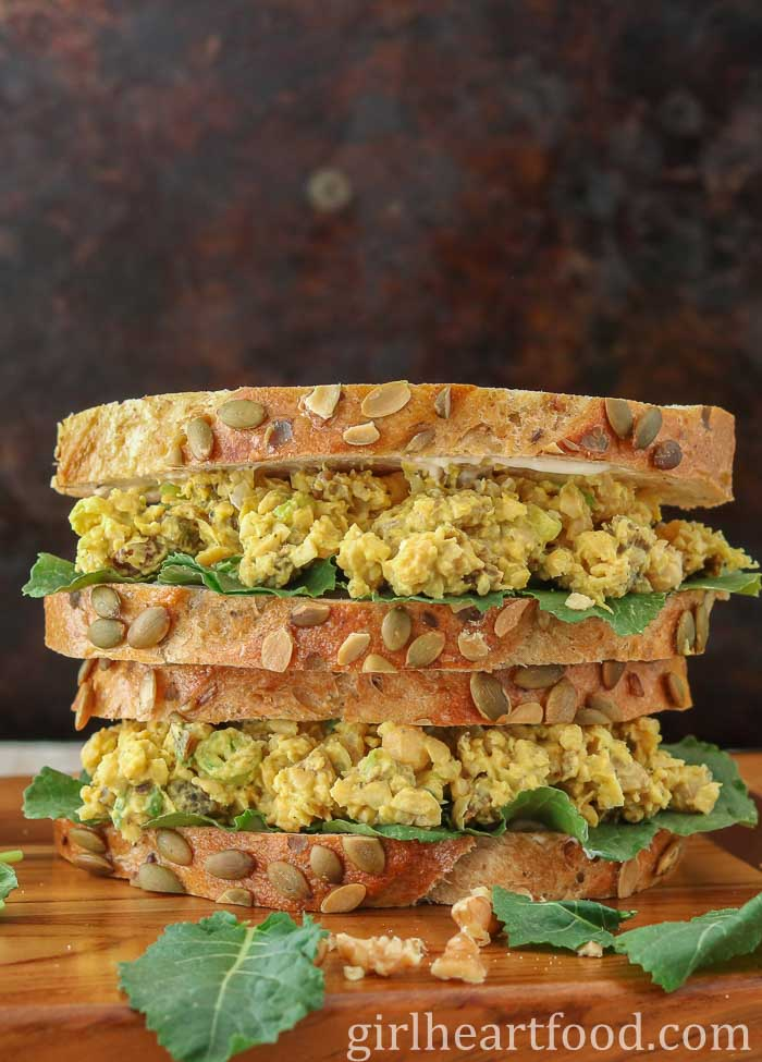 A stacked curried chickpea salad sandwich on a wooden board.