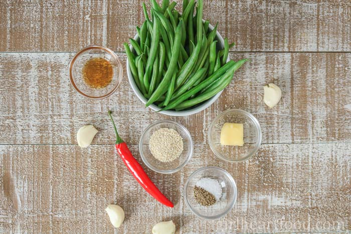 Ingredients for a garlicky green beans recipe on a wooden board.