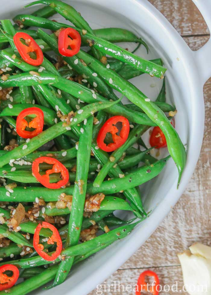 White dish of garlicky green beans topped with sliced chili pepper and sesame seeds.