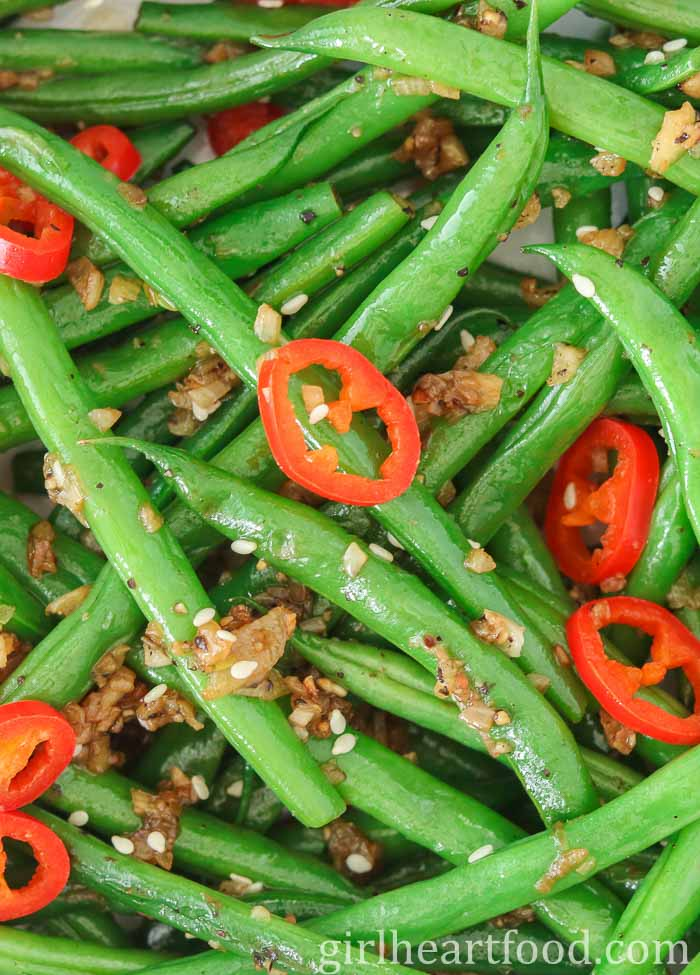 Close-up of garlic green beans with sliced chili pepper and sesame seeds.
