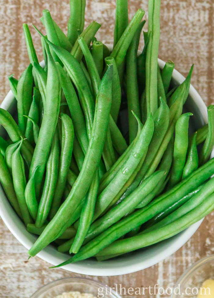 A white bowl of raw green beans.