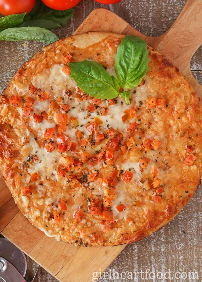 An overhead shot of a pizza with cheese, tomato and basil.
