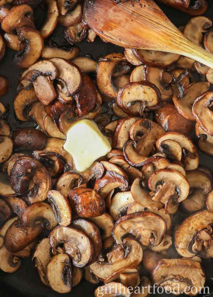 Sautéed mushrooms in a pan with a dab of butter and wooden spoon stirring them.