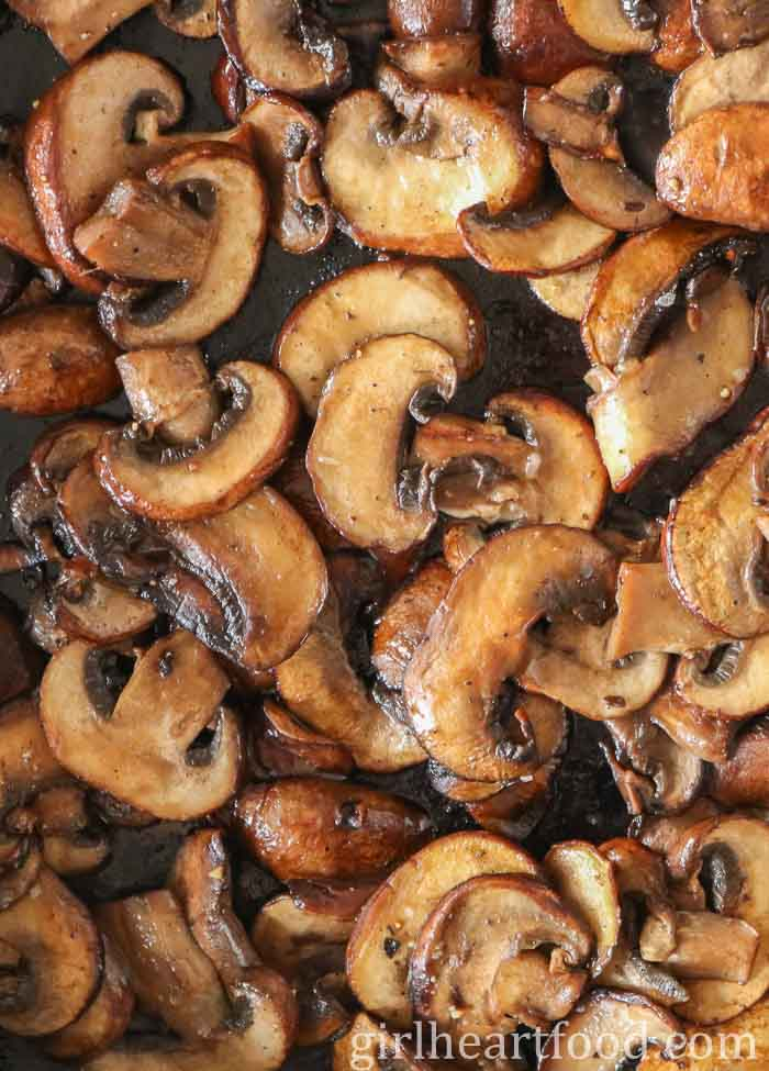 A close up shot of sauteed mushrooms in a pan.