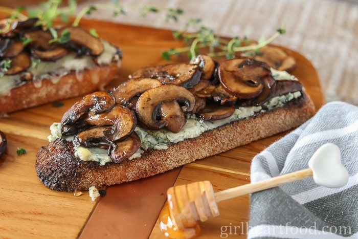 Toast with blue cheese, mushrooms and honey next to a honey stick.
