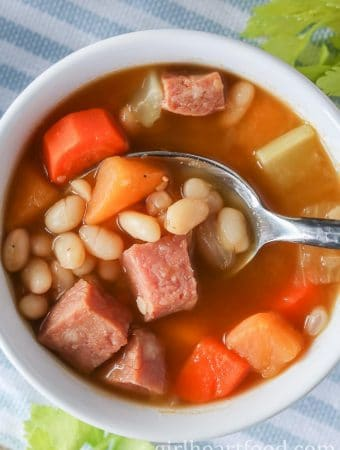 An overhead shot of a bowl of boiled beans with cubes of ham and veggies.