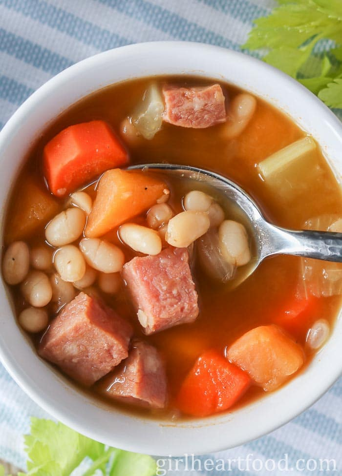 Bowl of boiled beans with cubes of ham and veggies and a spoon scooping some up.