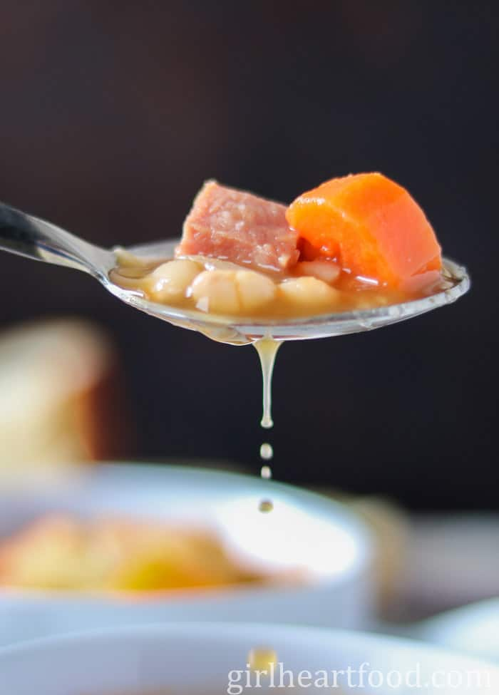 A spoonful of white beans, ham and carrot with broth dripping off the spoon.