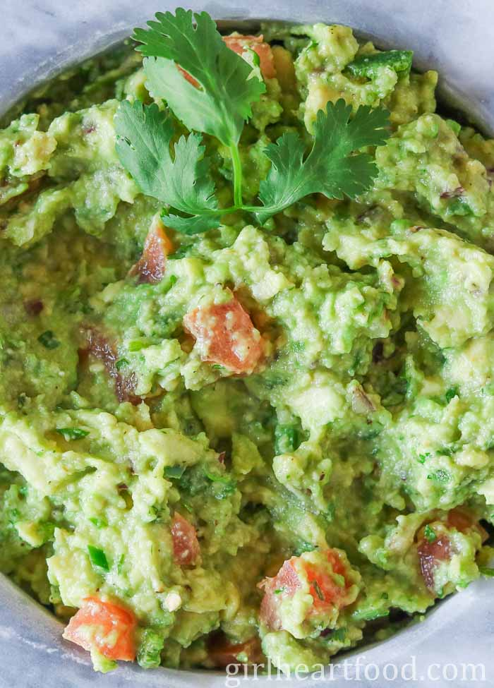 A close up shot of a bowl of guacamole dip garnished with cilantro.