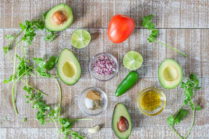 An overhead shot of ingredients for guacamole on a wooden board.