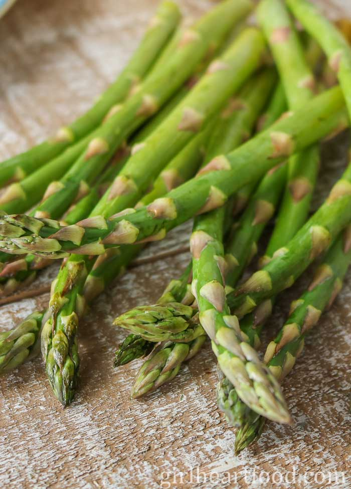 Raw asparagus on a wooden board.
