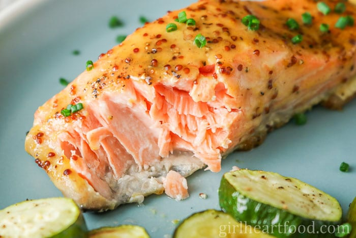 An oven baked salmon fillet that has been cut into to show interior on a blue plate.