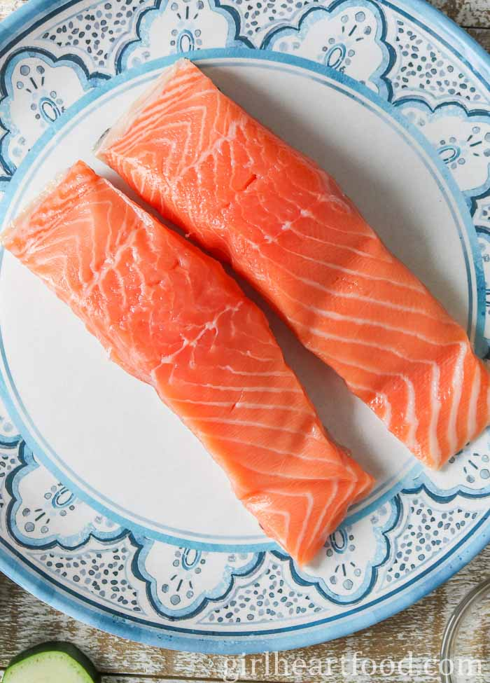 Two raw salmon fillets on a plate.