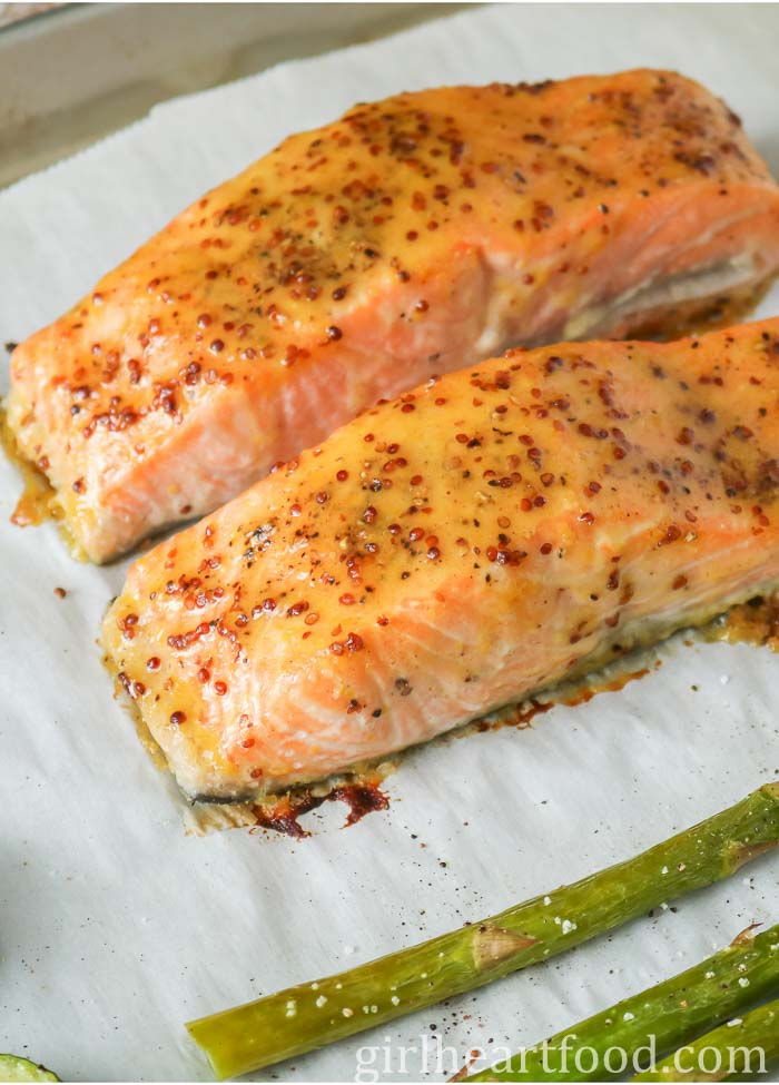 Cooked honey Dijon salmon fillets on a parchment lined sheet pan.