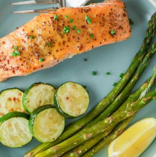 A piece of honey mustard salmon with vegetables on a blue plate.
