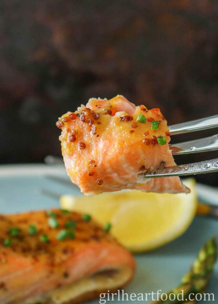 A forkful of a piece of honey mustard salmon.