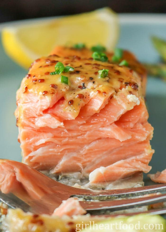 A close-up the interior of a fillet of oven-baked salmon, with a fork resting in front of it.