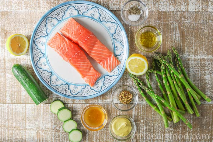 Ingredients needed for a sheet pan salmon and vegetable recipe on a wooden board.