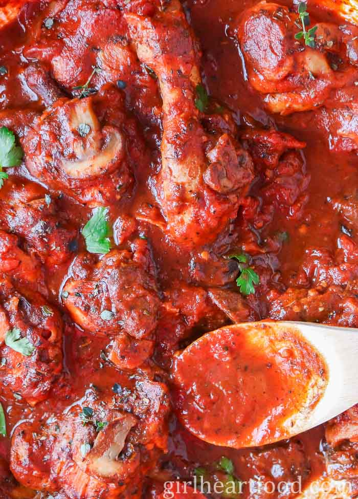 An overhead close up shot of chicken cacciatore with a wooden spoon in the pan garnished with fresh parsley and thyme.