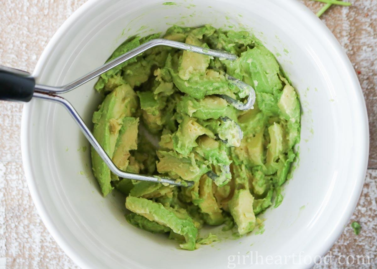 Mashing avocado in a white bowl with a potato masher.