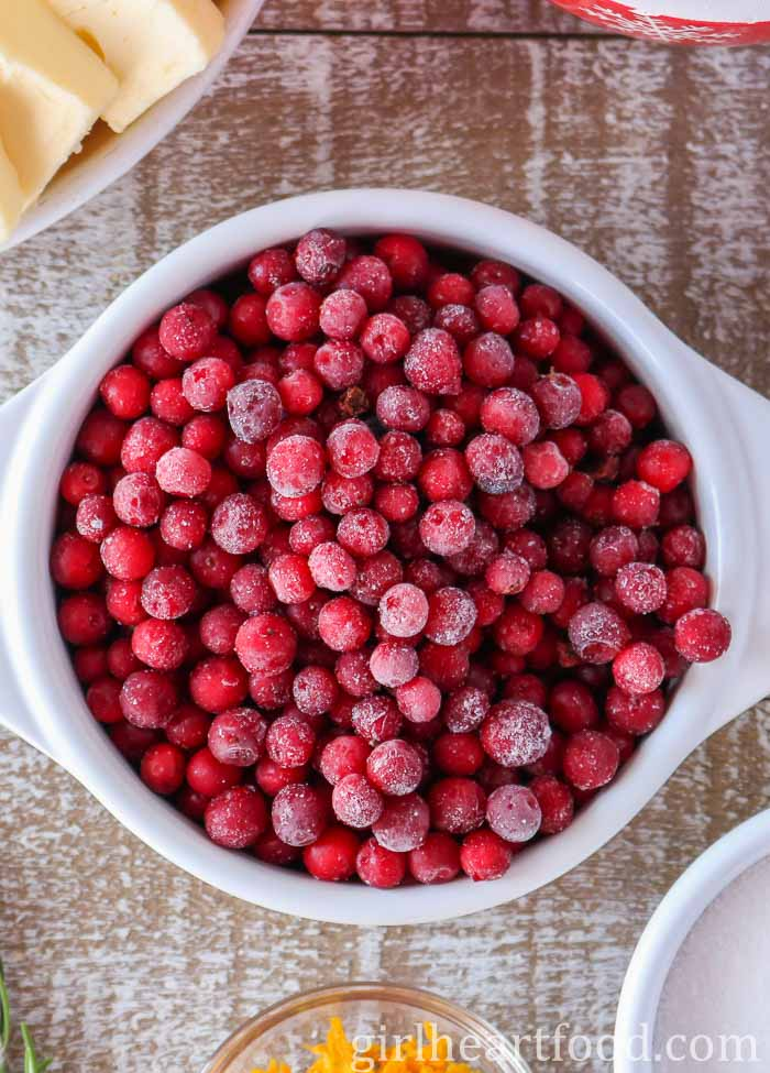 A white bowl filled with frozen Newfoundland partridgeberries.