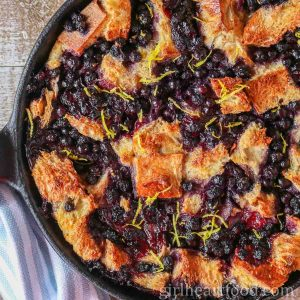 Blueberry bread pudding in a cast-iron skillet sprinkled with fresh lemon zest.