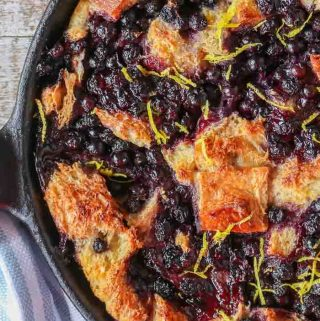 An overhead shot of a skillet blueberry bread pudding sprinkled with fresh lemon zest.