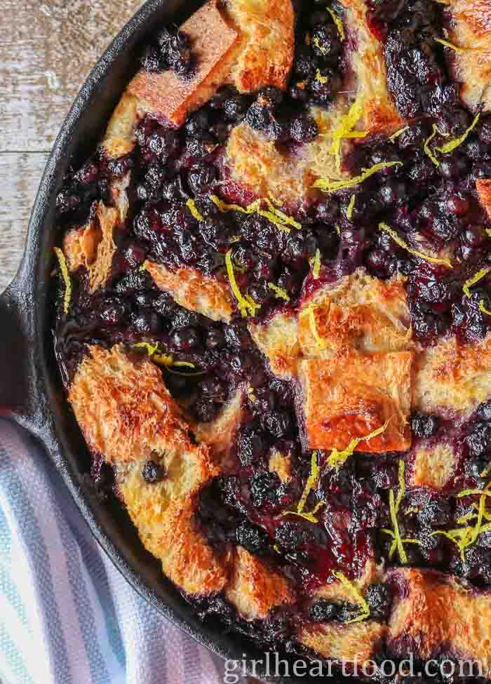 A cast iron blueberry bread pudding sprinkled with fresh lemon zest.