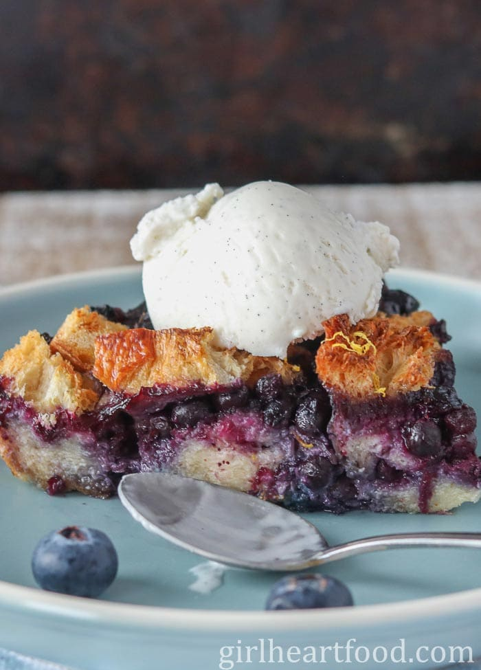 A piece of blueberry bread pudding topped with vanilla ice cream on a blue plate.