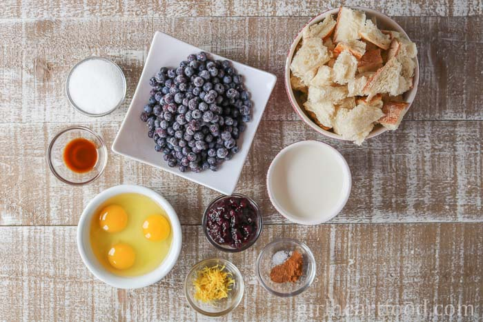 Ingredients for bread pudding made with blueberries on a wooden board.