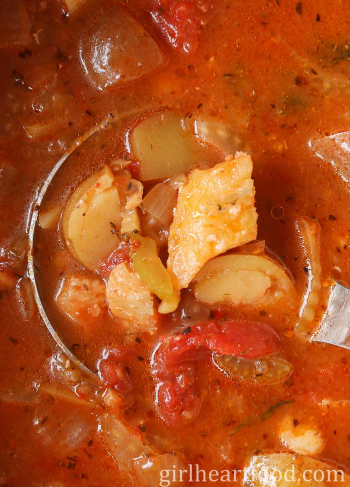 A close up overhead shot of a pot of cod fish stew with a ladle in the pot.