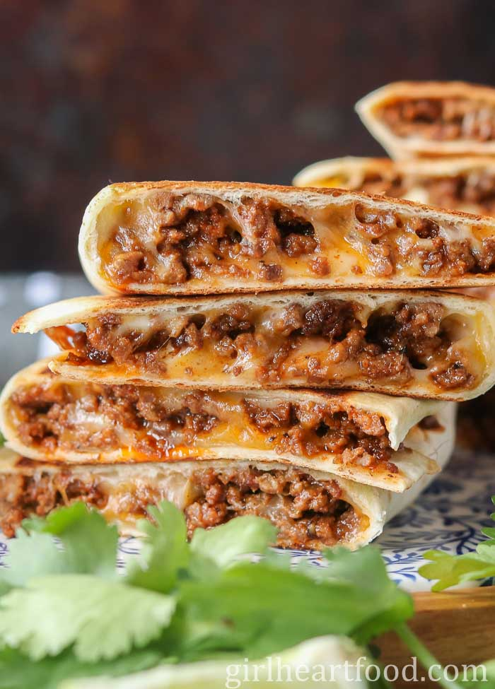A stack of ground beef quesadillas next to cilantro.