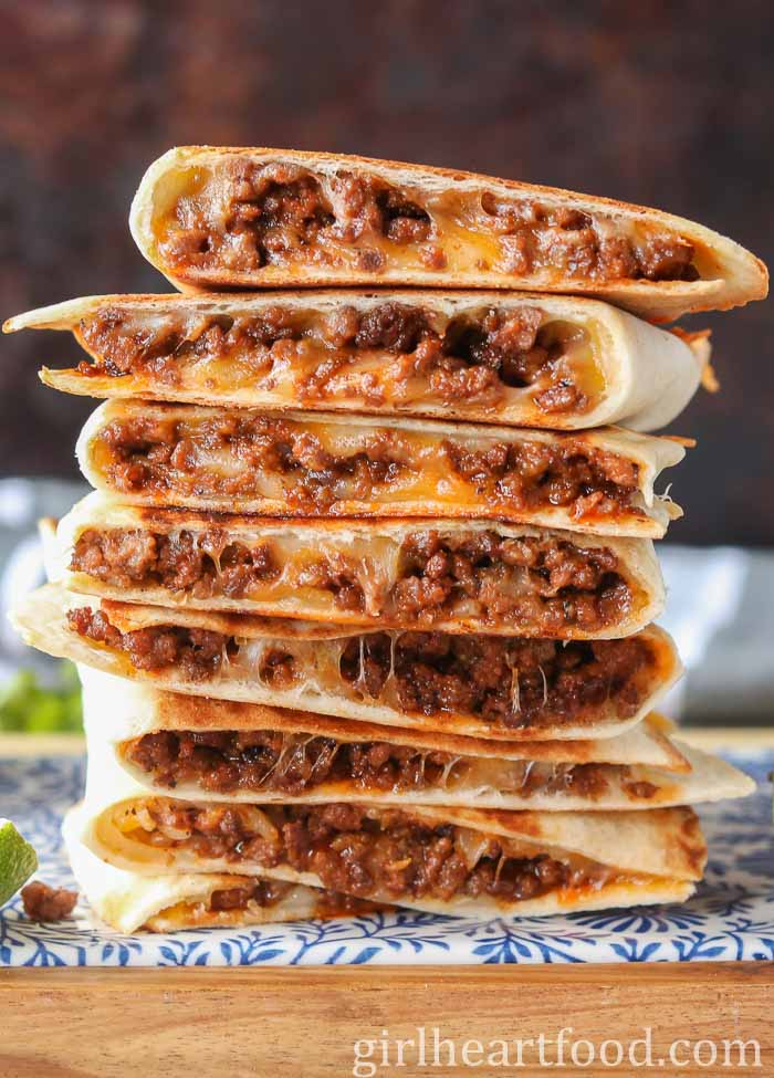 Tall stack of cheesy ground beef quesadillas on a blue and white platter.