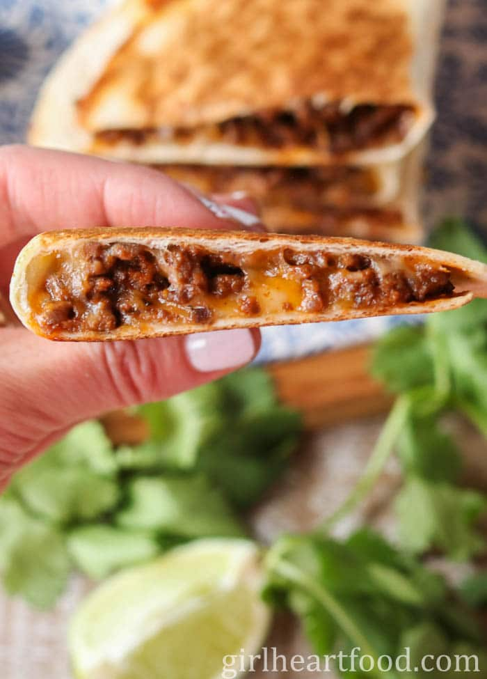 Holding up a cheese and beef quesadilla.